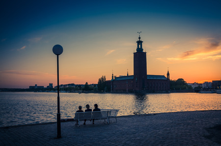 Silhouette of women sitting on bench at promenade quay bank of Lake Malaren looking at Stockholm City Hall Stadshuset tower building on Kungsholmen Island at sunset, dusk, twilight sky, Sweden Imagens