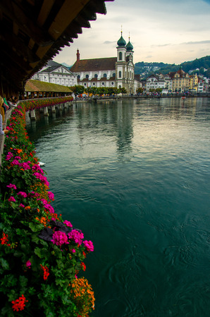 View of the historic city center of Luzern and Reuss river from famous wooden Chapel Bridge with blooming flowers, oldest wooden covered bridge in Europe, Luzern, Switzerland