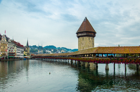 View of the historic city center of Luzern, Water Tower and wooden Chapel Bridge with blooming flowers on Reuss river, oldest wooden covered bridge in Europe , Luzern, Switzerland