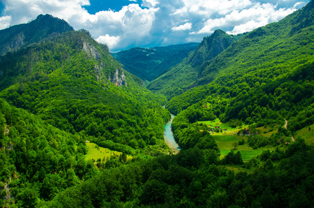 Mountain range and small village houses in green forest near Tara river gorge canyon, view from Durdevica Tara Bridge, Montenegro Stock Photo