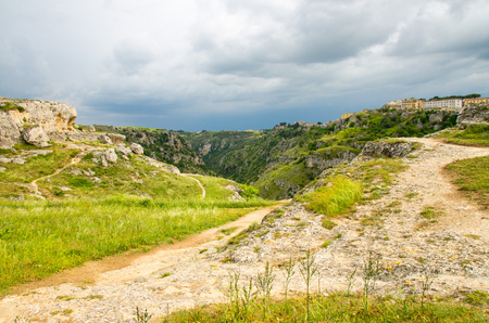 View of river valley with ravine canyon, rocks, green grass, path, caves di Murgia Timone and dark blue sky background near old ancient town Matera (Sassi), UNESCO Heritage, Basilicata, Southern Italy 版權商用圖片 - 111869436