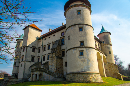 Old medieval castle in Nowy Wisnicz with towers and green lawn around, Poland