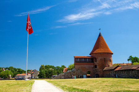 Medieval gothic Kaunas Castle with tower with red tiled roofs, red flag nearby and blue sky on background, Lithuania Redakční