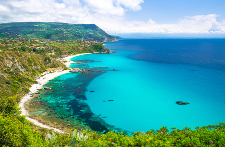 Aerial amazing tropical view of turquoise gulf bay, sandy beach, green mountains and plants, blue sky white clouds background from cliffs platform Cape Capo Vaticano Ricadi, Calabria, Southern Italy Stock Photo