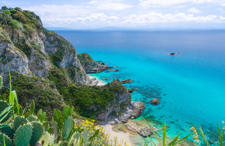 Rock cliff of cape Capo Vaticano Ricadi aerial panoramic view from Parco Belvedere platform, green grass hill with amazing blue azure turquoise water, blue sky background, Calabria, Southern Italy