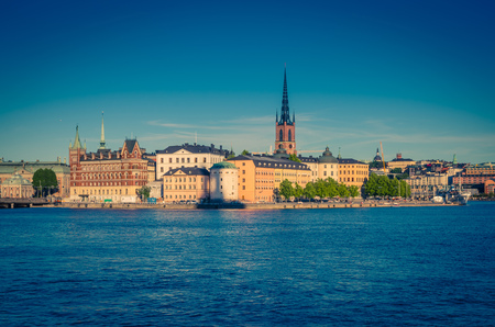 Riddarholmen island district with Riddarholm Church spires and typical sweden colorful gothic buildings, boat ship moored on Lake Malaren water from Kungsholmen with blue clear sky, Stockholm, Sweden