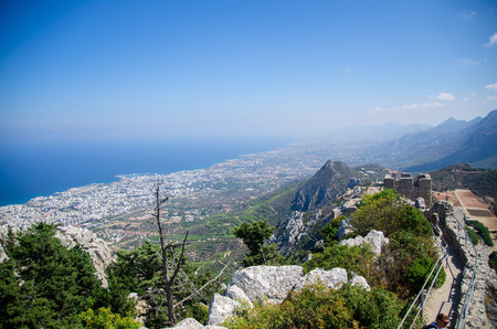 View of Kyrenia Girne mountains and town from medieval Saint Hilarion Castle in front of blue sky with white clouds and Mediterranean sea, Northern Cyprus