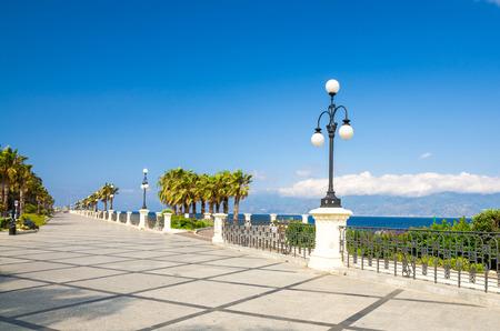 Paseo marítimo del muelle de Reggio di Calabria Lungomare Falcomata con vista del Estrecho de Messina conectado al mar Mediterráneo y Tirreno y al fondo de la isla de Sicilia, en el sur de Italia