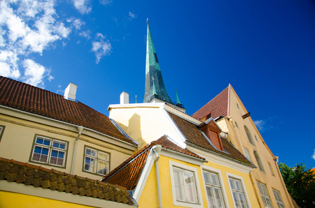 Medieval streets of Old Town of Tallinn with colourful buildings and St. Olaf's Church Tower, Estonia
