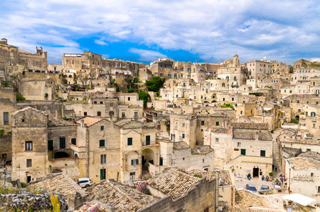 Sassi di Matera panoramic view of historical centre Sasso Caveoso of old ancient town with rock cave houses in front of blue sky and white clouds, Basilicata, Southern Italy