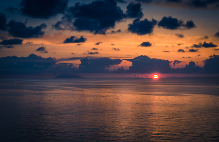 Aerial view of beautiful amazing sea sunset, ocean sunrise, seascape and endless horizon with color dramatic sky with clouds and volcanic hill mountain on background, Tropea, Calabria, Southern Italy