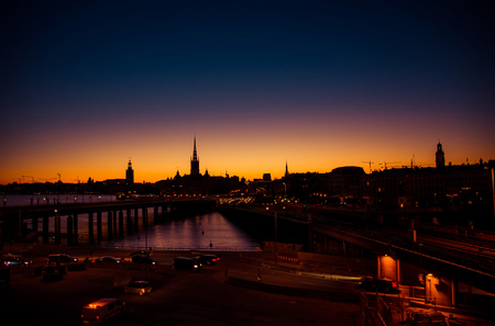 Silhouette of Stockholm cityscape skyline with Riddarholmen Church spires, City Hall Stadshuset tower, bridge over Lake Malaren in Gamla Stan at sunset, dusk, twilight and purple orange sky, Sweden