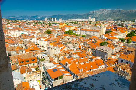 Old city buildings with orange roofs and Mosor Mountain aerial panoramic view from venetian Saint Domnius bell tower, Split, Dalmatia, Croatia