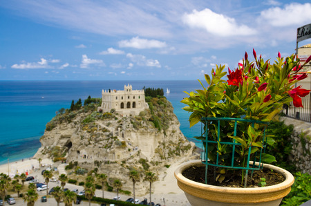Red flowers in flowerpot with blurred Monastery Sanctuary church Santa Maria dell Isola on top of rock, Tyrrhenian Sea, blue sky white clouds background, Tropea town, Calabria, Southern Italy