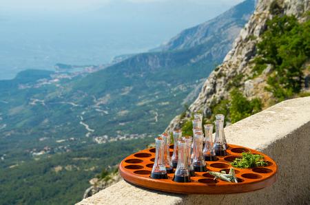 Tray with little wine bottles and parsley in front of hills and rocks of Biokovo mountain range and Makarska riviera Adriatic sea, Dalmatia, Croatia Stock Photo