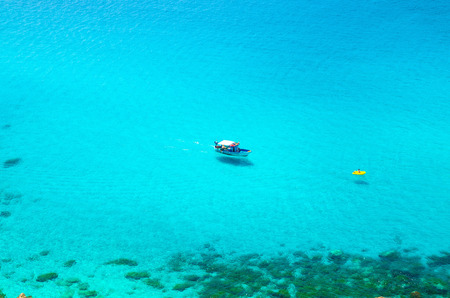 Fishing yacht and rubber boat sail drift on blue azure turquoise water surface of Tyrrhenian sea with shadows on bottom not far from cape Capo Vaticano Ricadi, Calabria, Southern Italy Stock Photo