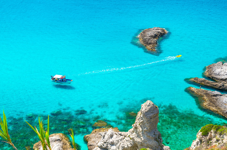 Fishing yacht with shadows on bottom sail drift and rubber boat with trail rush on waves of blue azure turquoise water surface of sea not far from cape Capo Vaticano Ricadi, Calabria, Southern Italy Stock Photo