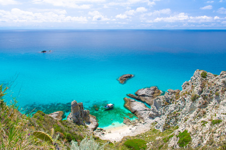 Aerial panoramic view of horizon and amazing tropical blue azure turquoise water of sea, rock cliff grass hill, yacht boat, blue sky background, Capo Vaticano, Calabria, Southern Italy