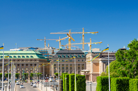 Riksplan, bushes and street with national flags on Sodermalm island, Gustav Adolfs torg square, Royal Swedish Opera house building, blue sky with yellow cranes background, Stockholm, Sweden