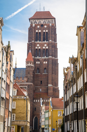 Brick tower of Basilica Assumption Blessed Virgin Mary St Marys Church Cathedral view from narrow street with typical colorful houses buildings in old historical town Gdansk, Poland 에디토리얼