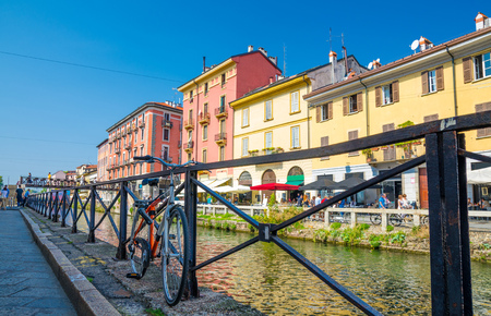 Bike near railing of Naviglio Grande grand canal waterway and typical colourful buildings on embankment, promenade in beautiful summer day with blue sky background, Milan, Lombardy, Italy 免版税图像