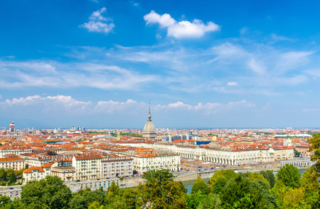 Aerial top panoramic view of Turin city center skyline with Piazza Vittorio Veneto square, Po river and Mole Antonelliana building with high spire, blue sky white clouds background, Piedmont, Italy
