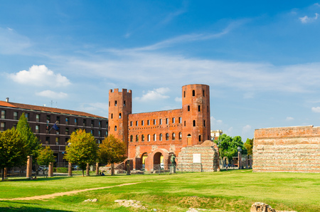 Palatine Gate Porta Palatina towers brick buildings is a Roman Age city ancient gate ruins with Julius Caesar statue and green lawn in historical centre of Turin Torino city, Piedmont, Italy