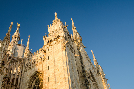 White walls of Duomo di Milano cathedral with high windows, spires, mouldings and stucco work, view from below with blue sky background, Milan historical city centre, Italy 스톡 콘텐츠