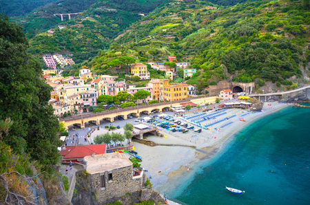 Top aerial view of green hill, railway, beach and harbor of Monterosso town village at sunset dusk, Genoa Gulf, Ligurian Sea, National park Cinque Terre, La Spezia, Liguria, Italy Stok Fotoğraf