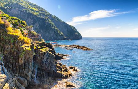 Rocks and cliffs coastline of Riviera di Levante of National park Cinque Terre Coast, Ligurian and Mediterranean Sea with blue sky in sunny day, copy space, Riomaggiore village, Liguria, Italy