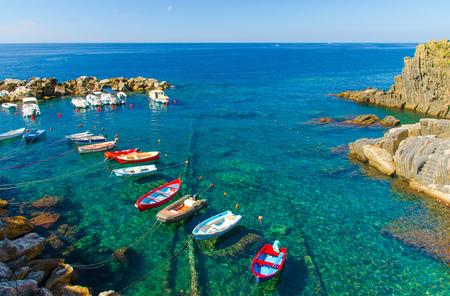 Fishing colorful boats on transparent water in small harbor of Riomaggiore village National park Cinque Terre, Ligurian and Mediterranean Sea, coastline of Riviera di Levante, Liguria, Italy