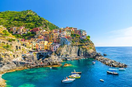 Manarola traditionelles typisch italienisches Dorf im Nationalpark Cinque Terre, bunte bunte Gebäudehäuser auf Felsklippe, Fischerboote auf dem Wasser, blauer Himmelshintergrund, La Spezia, Ligurien, Italien,