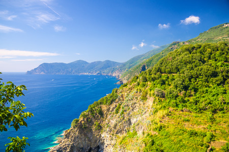 Aerial top panoramic view of green hills, rocks, cliffs and Gulf of Genoa, Ligurian Sea, coastline of Riviera di Levante, National park Cinque Terre, blue sky copy space, La Spezia, Liguria, Italy