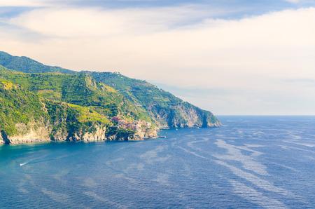 Aerial top panoramic view of Manarola village on cliff and Gulf of Genoa, Ligurian Sea, coastline of Riviera di Levante, National park Cinque Terre, blue sky copy space, La Spezia, Liguria, Italy