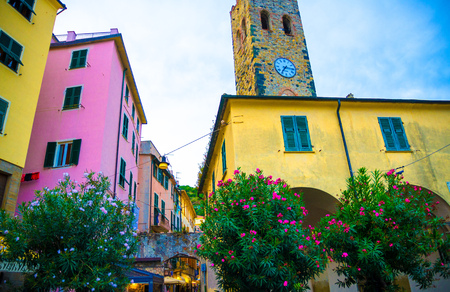 Catholic Church of San Giovanni Battista chiesa with clock tower, colorful buildings houses and flowers around in Monterosso village, National park Cinque Terre, La Spezia province, Liguria, Italy 免版税图像
