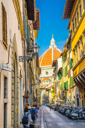 Dome of Florence Duomo, Cattedrale di Santa Maria del Fiore, Basilica of Saint Mary of the Flower Cathedral, view from narrow street in historical city centre, Tuscany, Italy