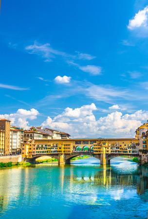 Ponte Vecchio Steinbrücke mit bunten Gebäuden Häuser über dem Fluss Arno blau reflektierendes Wasser im historischen Zentrum der Stadt Florenz, blauer Himmel weiße Wolken, vertikale Ausrichtung, Toskana, Italien