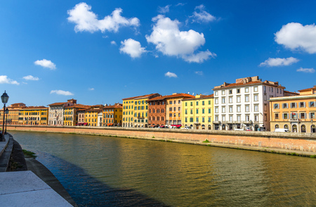 Row of old colorful buildings houses on embankment promenade of Arno river in historical centre of Pisa town with blue sky white clouds copy space background in sunny day, Tuscany, Italy