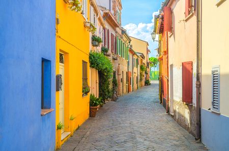 Typical italian cobblestone street with colorful multicolored buildings, traditional houses with green plants on walls and shutter windows in old historical city centre Rimini, Emilia-Romagna, Italy Reklamní fotografie
