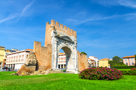 Ruins of ancient brick wall and stone gate Arch of Augustus Arco di Augusto, green lawn with bush of flowers in old historical touristic city centre Rimini, blue sky background, Emilia-Romagna, Italy Banque d'images