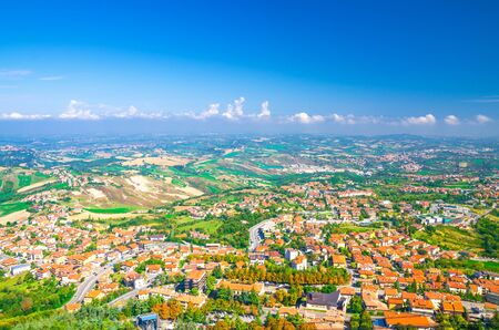 Aerial top panoramic view of landscape with valley, green hills, fields and villages of Republic San Marino suburban district with blue sky white clouds background. View from San Marino fortress