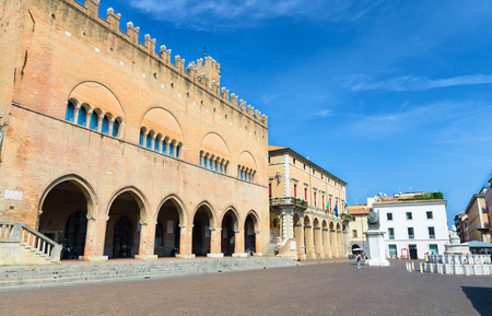 Palazzo dell'Arengo palace building with arches and Pope Paul V statue on Piazza Cavour square in old historical touristic city centre Rimini with blue sky background, Emilia-Romagna, Italy Sajtókép