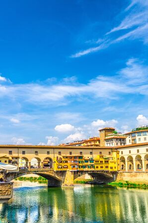 Ponte Vecchio stone bridge with colourful buildings houses over Arno River blue reflecting water in historical centre of Florence city, blue sky white clouds, vertical orientation, Tuscany, Italy