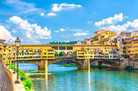 Ponte Vecchio stone bridge with colourful buildings houses over Arno River blue turquoise water and embankment promenade in historical centre of Florence city, blue sky white clouds, Tuscany, Italy