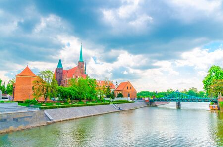 Sts. Peter and Paul church, Collegiate Church of Holy Cross and St. Bartholomew, alley with grass lawn, green trees and Tumski bridge over Oder river in old historical city centre of Wroclaw, Poland