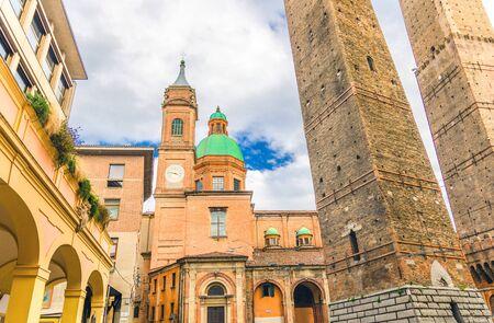 Two medieval towers of Bologna Le Due Torri: Asinelli and Garisenda and Chiesa di San Bartolomeo Gaetano church on Piazza di Porta Ravegnana square in old historical city centre, Emilia-Romagna, Italy Stock Photo