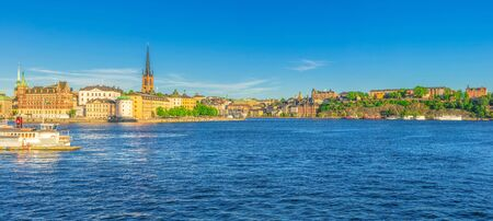 Panoramic view of Riddarholmen island district with Riddarholm Church spires, typical sweden colorful gothic buildings, Lake Malaren, Sodermalm island, blue clear sky background, Stockholm, Sweden