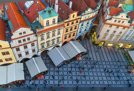 Top view of Prague Old Town (Stare Mesto) historical city centre. Row of buildings with colorful facades and red tiled roofs on Old Town Square Staromestske namesti in evening, Bohemia, Czech Republic