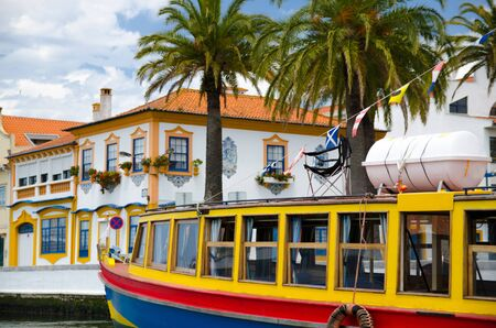 Portugal Aveiro in summer, little Venice of Portugal, Vouga river, Portugal Aveiro Chanel, typical tourist boat, colored boat on a background of palm trees, white vintage houses with painted windows