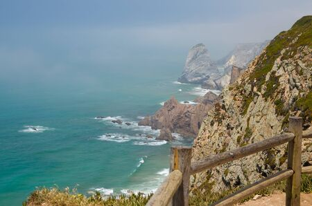 Portugal, Cabo da Roca, The Western Cape Roca of Europe, wooden railing around the lighthouse, ocean view from the Cape  Roca, cliff above the Atlantic ocean, azure water in the Atlantica
